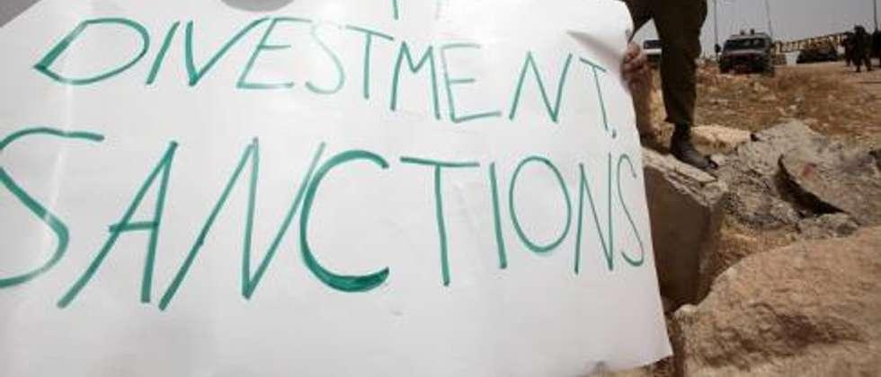 """Un Palestinien tient un panneau portant l'inscription """"Boycott, Divestment, Sanctions"""" (BDS) près de la colonie israélienne de Bat Ayin, à l'ouest d'Hébron (Cisjordanie), le 8 juin 2013 ( AFP/Hazem Bader )"""