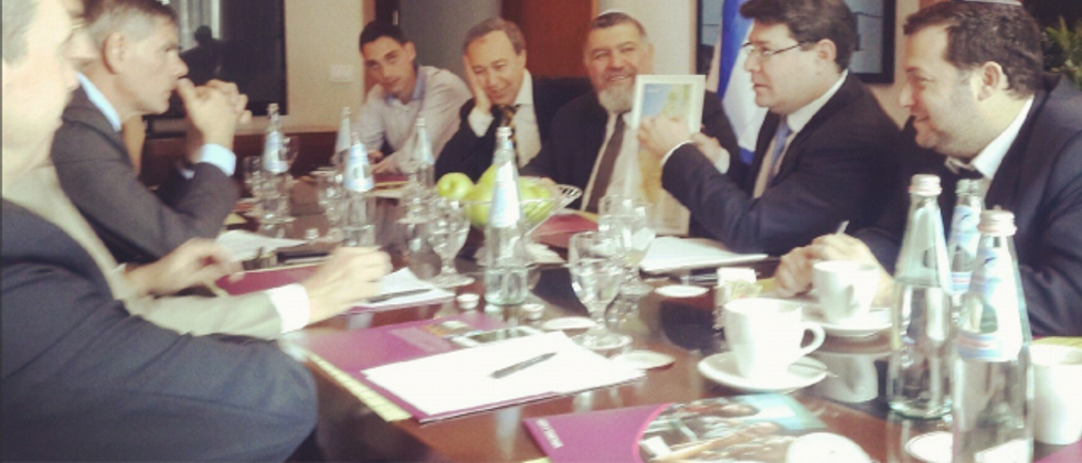 MK Ofir Akunis (holding map) meets with Flemish Interest delegates ( Facebook )