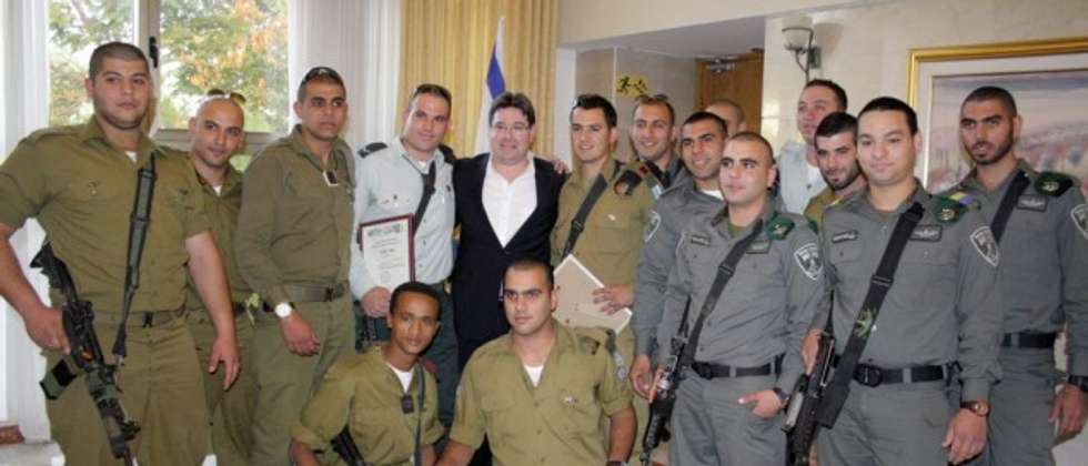 A Christian Arab soldier receiving a certificate of appreciation from Father Gabriel Naddaf during an event in Nazareth ( IDF Spokesperson's Unit )