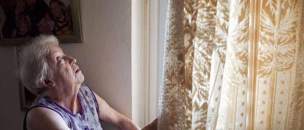 Holocaust survivor looks out window of her home in Ashkelon after rocket fell nearby ( Amcha )