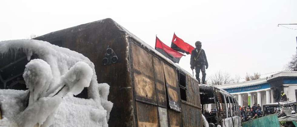 A protester stands on the roof of a burnt bus used as a part of a barricade as he watches anti-riot police in Kiev on January 21, 2014