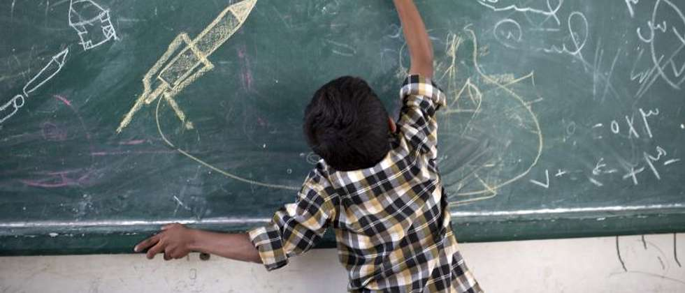 A Palestinian boy draws on a chalk board at a UN school after evacuating his home near the border in Gaza City on July 13, 2014 ( Mahmud Hams (AFP) )