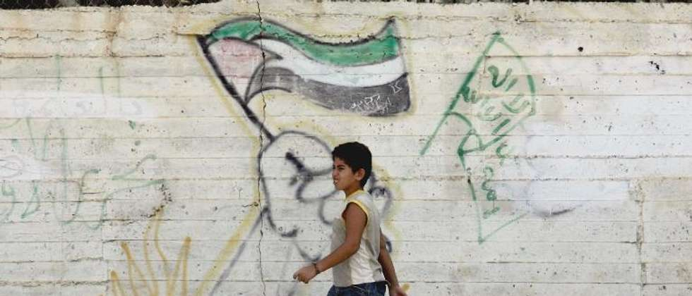 File picture shows Palestinian boy walking past graffiti of the Palestinian (L) and the Hamas' (R) flags in the West Bank Jenin refugee camp ( Saif Dahlah (AFP/File) )