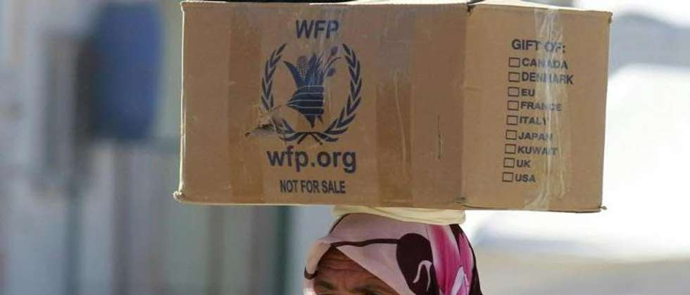A Syrian refugee carries on her head a box distributed by the World Food Programme as she walks through the Zaatari refugee camp in Jordan, on January 24, 2014 ( Khalil Mazraawi (AFP) )