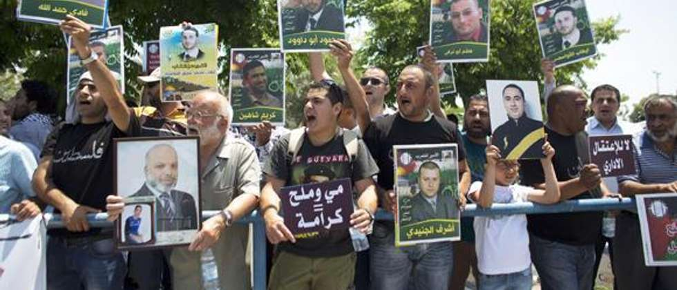 Palestinian activists hold placards during a protest outside the Israeli run Ayalon prison in Ramle, near Tel Aviv, calling for the release of Palestinian prisoners, on May 23, 2014, as they express solidarity with Palestinian prisoners who are on hunger  ( AFP )