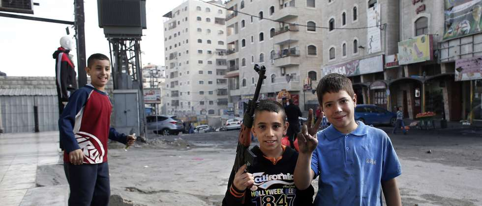 Palestinian boys with a toy gun in East Jerusalem neighborhood of Shuafat - Photo: AFP/Thomas Coex