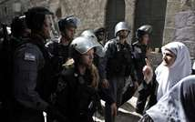A Palestinian woman gestures next to Israeli security forces as they temporarily close off access to the Al-Aqsa mosque compound in Jerusalem's Old City ( Ahmad Gharabli/AFP )
