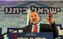 Foreign Minister Avigdor Lieberman speaks at a function of his Yisrael Beiteinu party with the Hebrew slogan that says: We keep our promise (Courtesy Ynet)