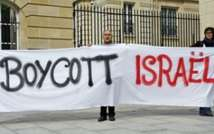 An anti-Israel activists holds up a banner calling for the boycott of Israel ( PHOTO: AFP. )