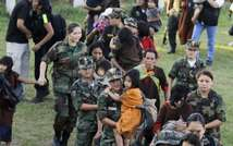 Peruvian army officers take adults and children to helicopters after they were freed on Monday (Luis Enrique Saldana/AFP)