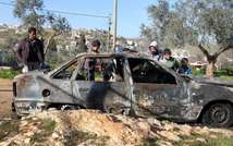 Palestinian children inspects a burnt car in the West Bank village of Qusra near Nablus on 21 February 2013. Israeli settlers torched seven cars in the northern West bank village of Qusra ( (Photo: AFP - Jaafar Ashtiyeh) )