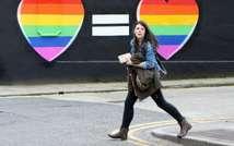 Une femme passe devant une affiche en faveur du mariage homosexuel en Irlande le 21 mai 2015 (PAUL FAITH (AFP))