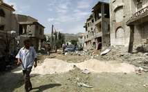 A Yemeni man walks past damaged buildings following an air-strike by the Saudi-led coalition on Sanaa, August 31, 2015 ( Mohammed Huwais (AFP/File) )
