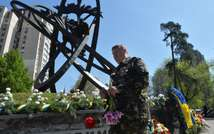 A former liquidator of the Chernobyl nuclear accident holds flowers at the victims' memorial in Kiev on April 26, 2014 (Sergei Supinsky (AFP/File))