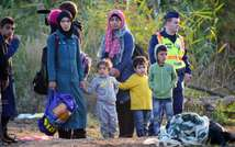 A group of migrant women and children escorted by police wait at a collector point near Roszke village at the Hungarian-Serbian border on August 28, 2015 ( Attila Kisbenedek (AFP) )