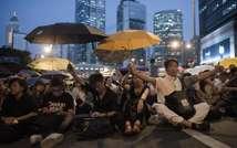 Des manifestants prodémocratie devant un écran géant installé dans le quartier Admiralty, à Hong Kong, retransmettant en direct les discussions entre gouvernement local et représentants des protestataires, le 21 octobre 2014 (Nicolas Asfouri (AFP))