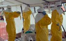 Liberian health workers don full protection outfits at an Ebola treatment centre in Monrovia, on October 18, 2014 (Zoom Dosso (AFP))