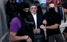 Nikos Michaloliakos entouré de policiers masqués à la sortie des locaux de la police le 28 septembre 2013 à Athènes ( Angelos Tzortzinis  (AFP) )