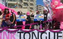 SAFRICPeople stand on a float holding signs saying 'Love Uganda, hate homophobia' in reaction to Uganda's law banning homosexuality during a parade on the streets of Green Point in Cape Town, South Africa, on March 1, 2014A-GAY-PRIDE ( Jennifer Bruce (AFP/File) )