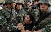 افراد من الجيش التايلاندي يعتقلون معارضا متظاهرا ضد الانقلاب في بانكوك ( كريستوف ارشامبو (اف ب) )