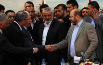 Palestinian Fatah envoy Azzam al-Ahmed (left) shakes hands with Hamas deputy leader Musa Abu Marzuk (right) in the presence of Hamas prime minister Ismail Haniya (centre) after signing a reconciliation agreement in Gaza City, on April 23, 2014 ( Said Khatib (AFP) )