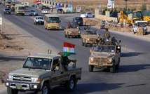 Kurdish peshmerga fighters drive in convoy through Arbil after leaving a base in northern Iraq on October 28, 2014 headed for the Syrian town of Kobane (Safin Hamed (AFP))
