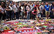 Members of the public look at tributes left in memory of victims of the Tunisia attacks, before observing a minute's silence in England, on July 3, 2015 (Oli Scarff (AFP/File))