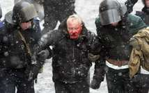 Ukrainian riot policemen detain a bleeding protester following clashes between security forces and pro-EU demonstrators in central Kiev on January 22, 2014 ( Anatolii Boiko (AFP) )