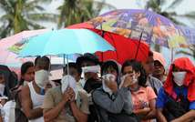 Des survivants se protègent de l'odeur des cadavres le 14 novembre 2013 à Taclogan ( Ted Aljibe (AFP) )