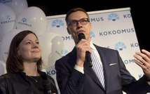 Alexander Stubb (R) and party secretary Minna Arve speak on stage after the announcing of the pre-elections votes at the party's parliamentary elections reception in Helsinki on April 19, 2015 ( Vesa Moilanen (Lehtikuva/AFP) )