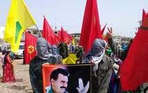 Masked Kurdish people hold a portait of jailed Kurdish rebel chief Abdullah Ocalan during a 2013 ceremony in Urfa, southeastern Turkey (AFP)
