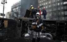 Un opposant, portant casque et masque à gaz, devant une barricade à Kiev, le 26 janvier 2014 ( Aris Messinis (AFP) )