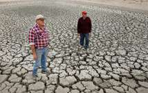 Farmer Marshall Rodda (L) and Gilbert Fryatt (R) stand in an empty dam during the country's worst drought in a century in the Australian wheat belt area of Wimmera, northwest of Melbourne, November 14 2006 ( William West (AFP/File) )