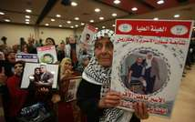Relatives of Palestinian prisoners held in Israeli prisons hold portraits of their loved-ones in the West Bank city of Ramallah on March 27, 2014 ( Abbas Momani (AFP/File) )