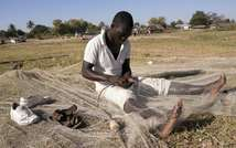 A fisherman fixes a net on the shores of Lake Malawi, near the Makawa Fishing Village in the district of Mangochi on May 18, 2014 ( Amos Gumulira (AFP/File) )