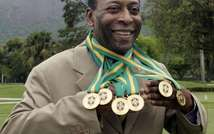 Brazilian football legend Pele poses with his six Brazil's champion medals on December 22, 2010 during a ceremony in Rio de Janeiro, Brazil ( Caio Leal (AFP/File) )