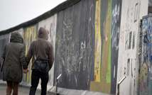 This file photo shows a couple walking along a preserved section of the Berlin Wall, on February 28, 2013 (Odd Andersen (AFP/File))
