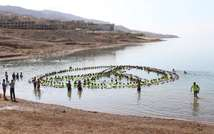 The largest floating human image showing a peace sign at the lowest point on earth, at the Dead Sea Spa Hotel Beach.