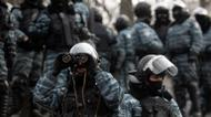 credits/photos : A Ukrainian police officer looks through binoculars at opposition activists after violent clashes in Kiev, on January 21, 2014