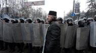 credits/photos : A Ukrainian priest walks past riot police after violent clashes in central Kiev, on January 21, 2014