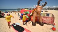 crédits/photos : Surf lifesavers (L) walk past a Christmas tree and an inflatable reindeer on Bondi Beach on Christmas Day in Sydney