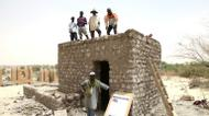 credits/photos : Workers pose during the reconstruction of a mausoleum in the Three Saints cemetery on April 8, 2015 in Timbuktu, northern Mali