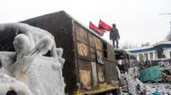 credits/photos : A protester stands on the roof of a burnt bus used as a part of a barricade as he watches anti-riot police in Kiev on January 21, 2014