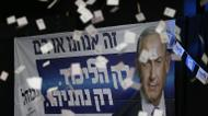 credits/photos : Confetti falls in front of a poster of Israeli Prime Minister Benjamin Netanyahu as supporters of his Likud party wait for election results