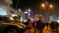 credits/photos : Iraqi walk past security forces as they gather at the al-Mansour square during Christmas and New Years eve celebrations in the capital Baghdad on December 31, 2016