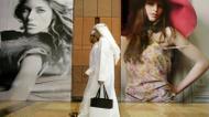ائتمانات/صور : اماراتيان يمران امام لوحات اعلانية في دبي في 9 اذار/مارس 2009