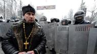 credits/photos : A Ukrainian priest walks past riot police in the center of Kiev, on January 22, 2014