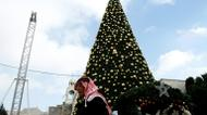 credits/photos : A Palestinian man walks past a Christmas tree at the Manger Square near the Church of the Nativity
