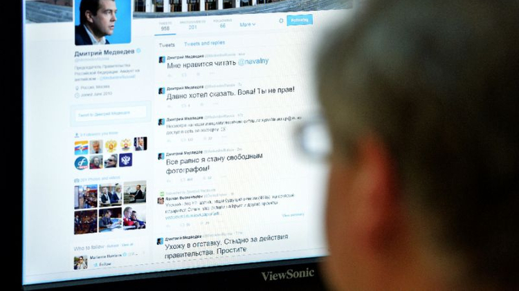 File photo: A man looks at the computer screen with the twitter page of Russian Prime Minister Dmitry Medvedev displayed, in Moscow on August 14, 2014