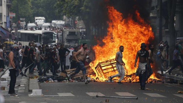 Protesters run by a fire barricade near the aerial metro station of Barbes-Rochechouart, in Paris, on July 19, 2014